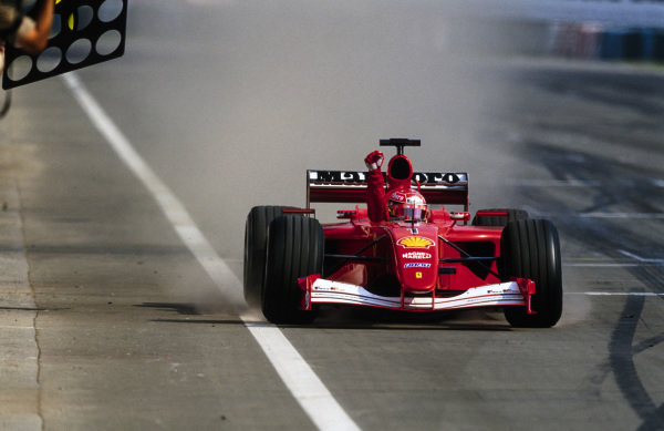 Michael Schumacher, Ferrari F2001, celebrates as he crosses the finish line to secure the race victory and clinch the world drivers' championship for a fourth time.