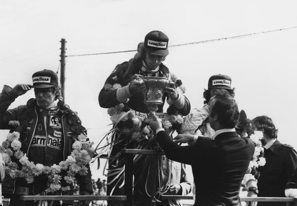 Silverstone, England. 14th - 16th July 1977. James Hunt (McLaren M26-Ford), 1st position, receives his winner's trophy from HRH Prince Michael of Kent with Niki Lauda (Ferrari 312T2), 2nd position and Gunnar Nilsson (Lotus 78-Ford), 3rd position, podium, portrait.  World Copyright: LAT Photographic.  Ref:  B/W Print.
