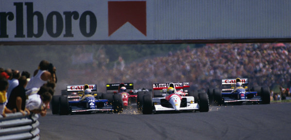 Ayrton Senna, McLaren MP4-6 Honda, with sparks flying as he brakes, leads Riccardo Patrese, Williams FW14 Renault, Alain Prost, Ferrari 643, and Nigel Mansell, Williams FW14 Renault, into the first corner at the start.