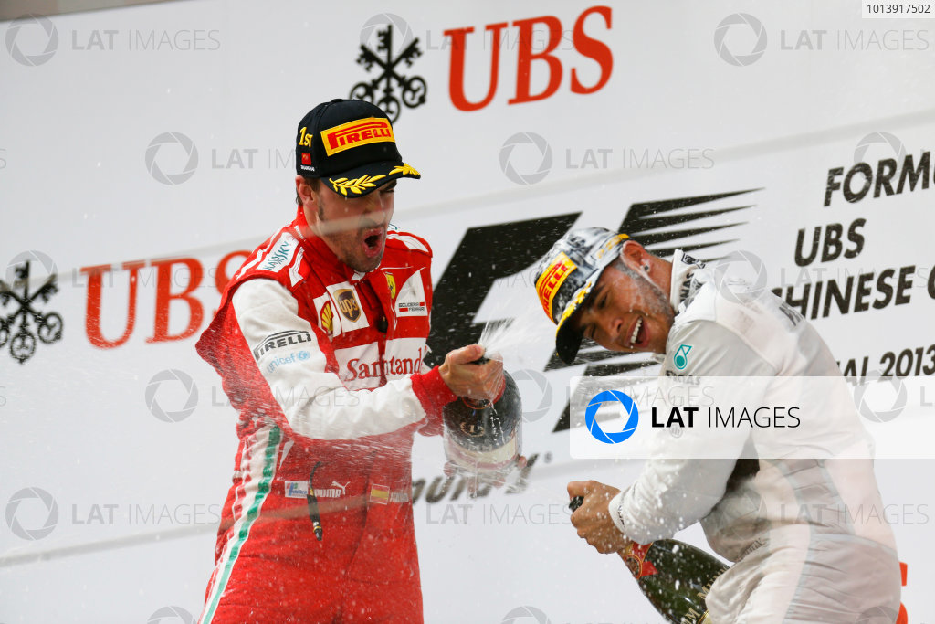 Shanghai International Circuit, Shanghai, China Sunday 14th April 2013 Fernando Alonso, Ferrari, 1st position, and Lewis Hamilton, Mercedes AMG, 3rd position, celebrate with Champagne on the podium. World Copyright: Alastair Staley/LAT Photographic ref: Digital Image _R6T2495