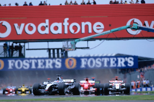 2004 British Grand PrixSilverstone England. 9th - 11th July.Kimi Raikkonen, McLaren Mercedes MP4/19 leads the field into the first corner at the start of the race. Action. World Copyright:Charles Coates/LAT Photographic Ref:35mm image A05