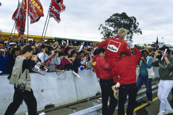 Stefan Johansson is hoisted onto the shoulders of a pair of Ferrari mechanics as he is greeted by many fans.