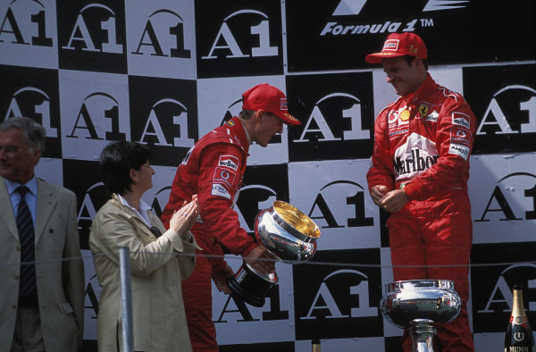 Michael Schumacher, race winner but standing in 2nd position, bows to Rubens Barrichello, 2nd position but standing on the top step of the podium.