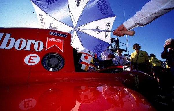 """1995 Portuguese Grand Prix.Estoril, Portugal.22-24 September 1995.Gerhard Berger (Ferrari 412T2) 4th position, on the grid before the start. He wore a different crash helmet as part of a competition run by a newspaper in Italy. The winning design was called """"No war in the World"""". Berger was only supposed to wear it on Friday, but he liked it so much that he wore it all weekend.World Copyright - LAT Photographic"""