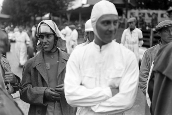 Tazio Nuvolari stands amongst a group of drivers on the grid.