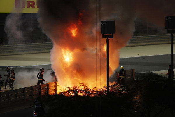 Fire marshals attend an inferno after Romain Grosjean, Haas VF-20, crashed heavily on the opening lap of the Bahrain Grand Prix. The race was stopped. Romain Grosjean, Haas F1, is escorted away on the left of the picture