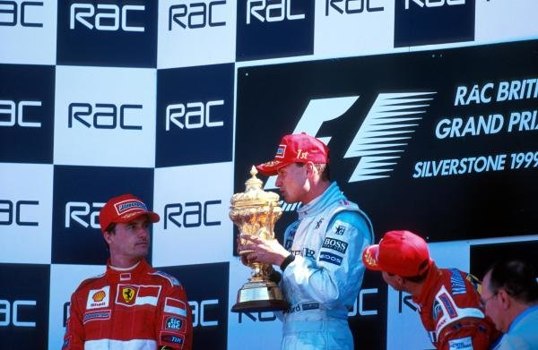 (L to R): Second placed Eddie Irvine (IRL) Ferrari, race winner David Coulthard (GBR) McLaren and third placed Ralf Schumacher (GER) Williams celebrate on the podium. Formula One World Championship, Rd8, British Grand Prix, Silverstone, 11th July 1999.