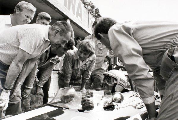 1969 Italian Grand Prix.Monza, Italy. 7 September 1969.Jack Brabham, Brabham BT26-Ford, retired, returned to racing at Monza. Here he talks to his engineers/mechanics including designer Ron Tauranac (left) and Ron Dennis (right), portrait, helmet.World Copyright: LAT PhotographicRef: Motor b&w print