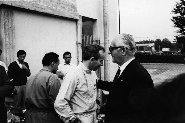 Monza, Italy. 6th September 1964. Rd 8. John Surtees with Ferrari team boss Enzo Ferrari talk in the pits, portrait.World Copyright: LAT Photographic