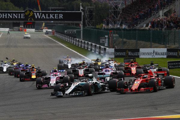 Lewis Hamilton, Mercedes AMG F1 W09, leads Sebastian Vettel, Ferrari SF71H, Sergio Perez, Racing Point Force India VJM11, Esteban Ocon, Racing Point Force India VJM11, Romain Grosjean, Haas F1 Team VF-18, and the rest of the field at the start. Nico Hulkenberg, Renault Sport F1 Team R.S. 18. locks-up in the background.