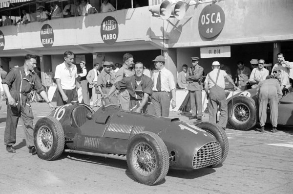 Peter Whitehead's Ferrari 125 being pushed down the pit lane.