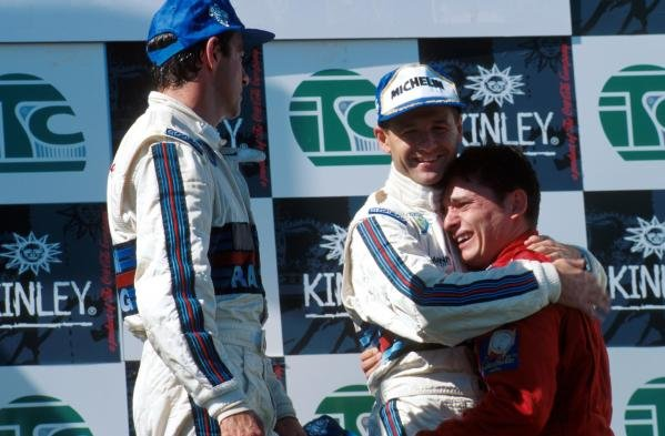 An emotional third place finisher Giancarlo Fisichella (ITA) Alfa Romeo is hugged by second place finisher Nicola Larini ITA) Alfa Romeo, whilst race winner Alessandro Nannini (ITA) Alfa Romeo looks on. International Touring Car Championship, Magny-Cours, France, 15 September 1996.