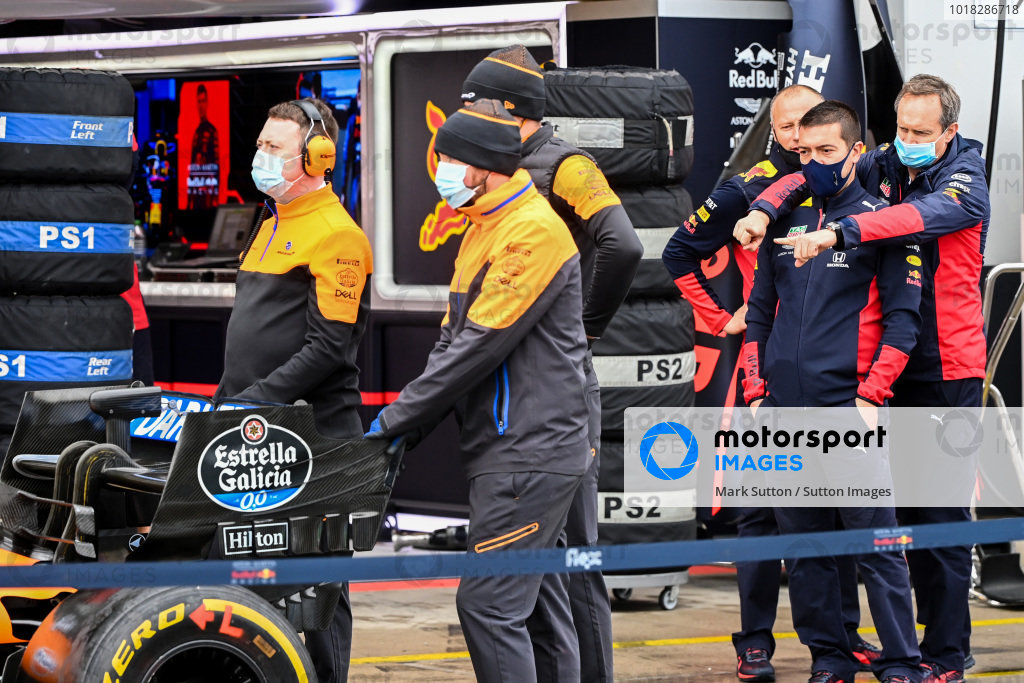 Red Bull mechanics point something out on the McLaren MCL35