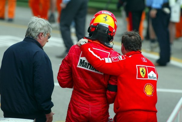 (L to R): Herbie Blash (GBR) FIA Delegate; Michael Schumacher (GER) Ferrari is comforted by Jean Todt (FRA) Ferrari General Manager after an impressive win following the death of his mother.Formula One World Championship, Rd4, San Marino Grand Prix, Race Day, Imola, Italy, 20 April 2003.DIGITAL IMAGE