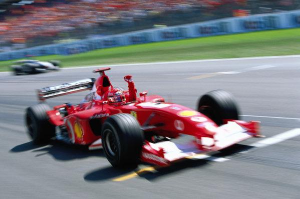 Michael Schumacher, Ferrari F2002, celebrates as he crosses the finish line.