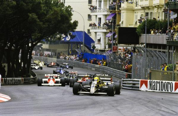 Ayrton Senna, Lotus 97T Renault, leads Nigel Mansell, Williams FW10 Honda, Alain Prost, McLaren MP4-2B TAG, and Michele Alboreto, Ferrari 156/85, through St. Devote at the start.