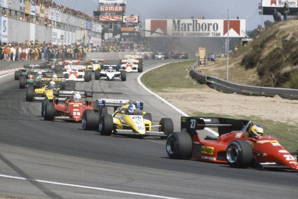 Michele Alboreto, Ferrari 126C4, leads Derek Warwick, Renault RE50, René Arnoux, Ferrari 126C4, Manfred Winkelhock, ATS D7 BMW, Riccardo Patrese, Alfa Romeo 184T, Eddie Cheever, Alfa Romeo 184T, and Alain Prost, McLaren MP4-2 TAG, at the start.