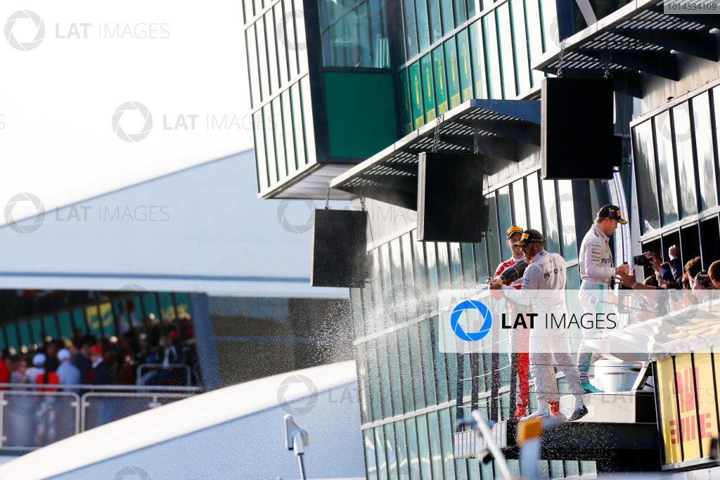 Albert Park, Melbourne, Australia. Sunday 20 March 2016. Lewis Hamilton, Mercedes F1 W07 Hybrid, Sebastian Vettel, Ferrari SF16-H and Nico Rosberg, Mercedes F1 W07 Hybrid celebrate on the podium after the race. World Copyright: Sam Bloxham/LAT Photographic ref: Digital Image _R6T4328
