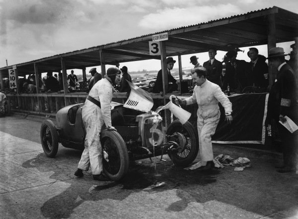 Brooklands, Great Britain.7 August 1926. Gillow, George Eyston (Aston-Martin GP) mechanic, pouring water over the cars radiator in an endeavour to cool it. A blown-out gasket put this car out. World Copyright: LAT Photographic. Ref: Autocar Glass Plate A6538.