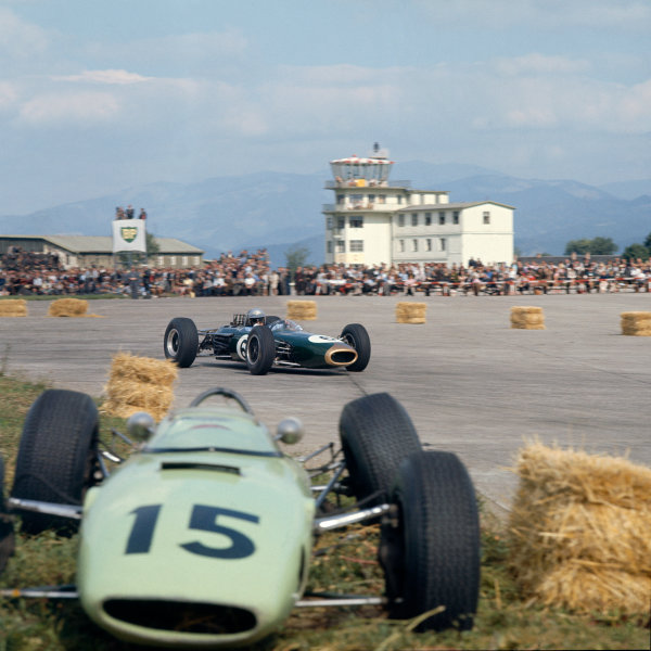 Zeltweg, Austria. 21-23 August 1964. Jack Brabham (Brabham BT11 Climax) passes the crashed car of Trevor Taylor (BRP 1 BRM). Ref: 1403. World Copyright: LAT Photographic.
