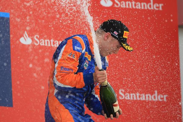 2013 GP2 Series. Round 5. Silverstone, Northamptonshire, England. 30th June. Sunday Race. Jon Lancaster (GBR, Hilmer Motorsport) celebrates his victory on the podium. World Copyright: Jakob Ebrey/GP2 Series Media Service. Ref: JE2_4655
