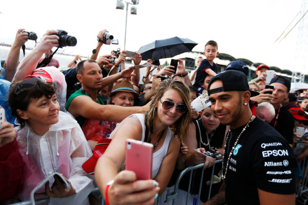 Hungaroring, Budapest, Hungary. Thursday 23 July 2015. Lewis Hamilton, Mercedes AMG, with a fan. World Copyright: Charles Coates/LAT Photographic ref: Digital Image _N7T1862