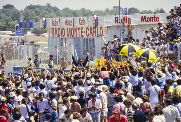 René Arnoux, 1st position, celebrates victory in front of fans.