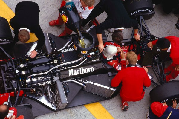 1987 Hungarian Grand Prix. Hungaroring, Budapest, Hungary. 7-9 August 1987. Alain Prost sits in his McLaren MP4/3 TAG Porsche while the mechanics get to work on the car and refuel.  Ref-87 HUN 09. World Copyright - LAT Photographic
