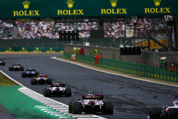 Carlos Sainz Jr., McLaren MCL34, leads Kimi Raikkonen, Alfa Romeo Racing C38, and Antonio Giovinazzi, Alfa Romeo Racing C38
