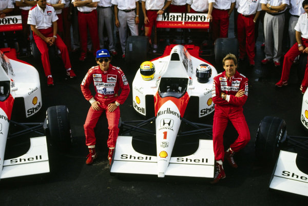Ayrton Senna and Gerhard Berger sit on the front wheels of Senna's McLaren MP4-6 Honda.