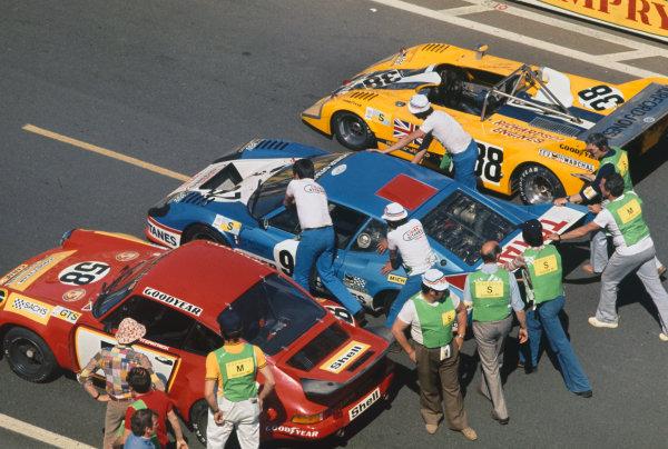 Le Mans, France. 14-15 June 1975 The cars of John Fitzpatrick/Gijs van Lennep/ Manfred Schurti/ Manfred Schurti (Porsche Carrera RSR), 5th position, Jean-Pierre Beltoise/Jean-Pierre Jarier (Ligier JS2 Maserati), retired, and Nigel Clarkson/Derek Worthington (Lola T292 Ford), 29th position, are pushed onto the grid, action. World Copyright: LAT PhotographicRef: 75LM06.