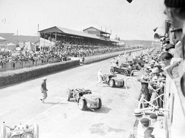 The drivers run to their cars at the start of the race.