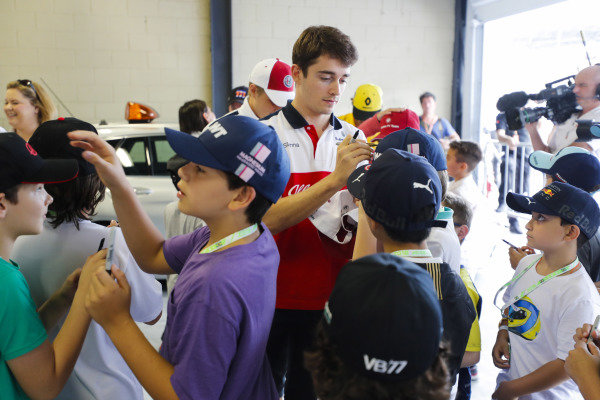 Charles Leclerc, Sauber, signs autographs for young fans.