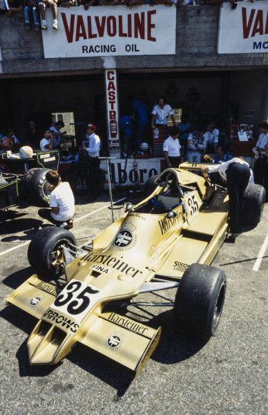 Riccardo Patrese waits at the rear of his Arrows A1 Ford as mechanics work on the car.