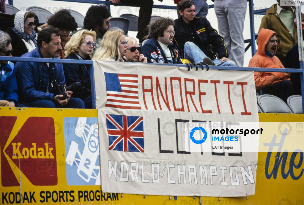 A banner in the crowd showing support for Mario Andretti and Team Lotus.