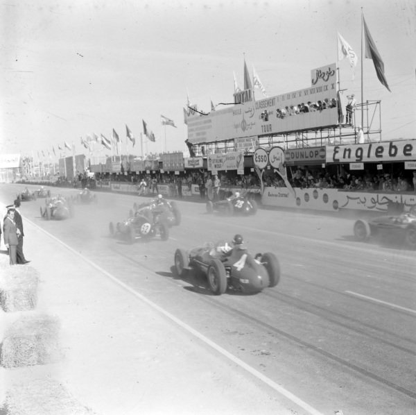 Mike Hawthorn, Ferrari Dino 156 #4, chases after Jack Brabham, Cooper T43 Climax #32, at the start of the race.