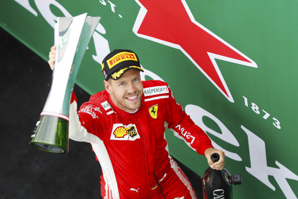 Sebastian Vettel, Ferrari, raises his winner's trophy on the podium.