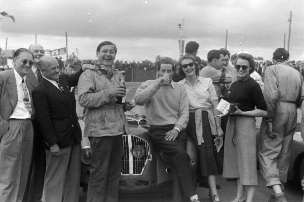 Duncan Hamilton and Tony Rolt celebrate with Champagne after the race.