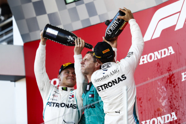 Valtteri Bottas, Mercedes AMG F1, 2nd position, and Lewis Hamilton, Mercedes AMG F1, 1st position, pour Champagne on their team mate on the podium