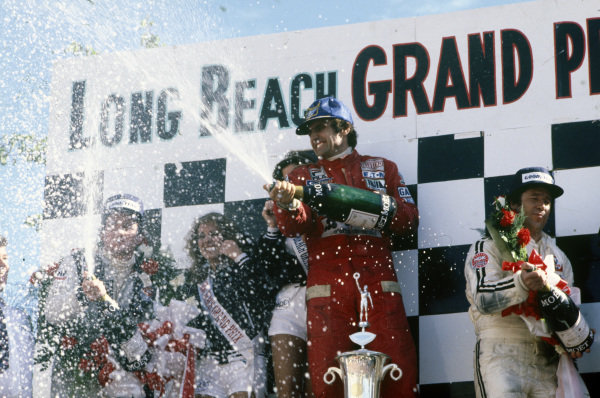 Carlos Reutemann celebrates victory on the podium with Mario Andretti, 2nd position, and Patrick Depailler, 3rd position.