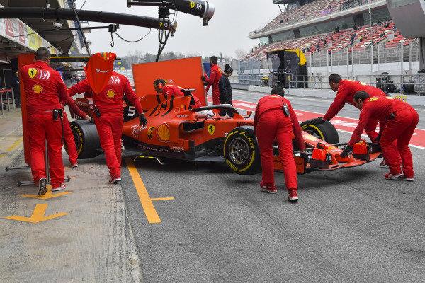 Sebastian Vettel, Ferrari, makes a pit stop, and team members shield the car from prying eyes