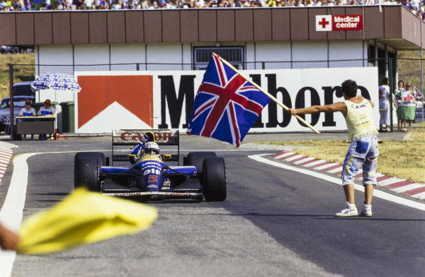 Nigel Mansell, Williams FW14B Renault, celebrates his world championship victory as a fan waves a Union Flag.