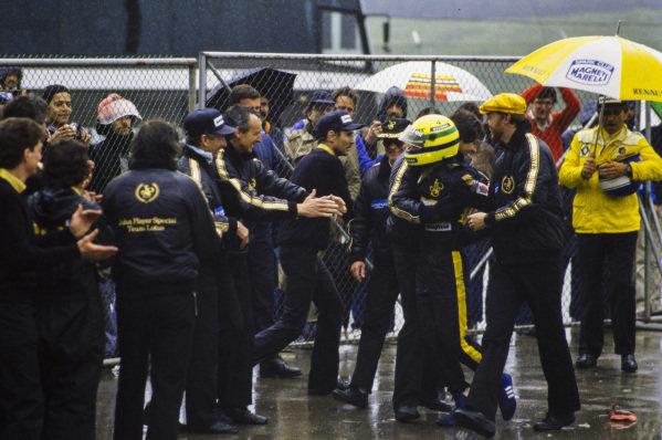 Ayrton Senna celebrates his first grand prix victory with the Lotus team. Engineer Steve Hallam, tyre man Kenny Szymanski and Gerard Ducarouge are visible.