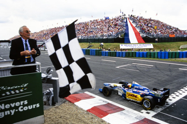 Michael Schumacher, Benetton B195 Renault, crosses the finish line and takes the chequered flag.