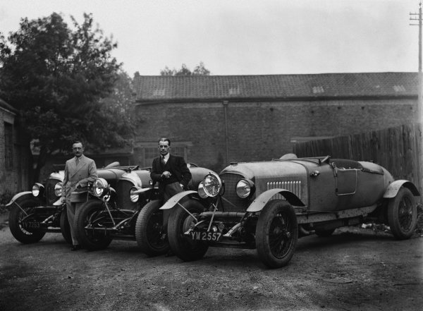 """The Bentley 4-1/2 litre team cars for the 1929 Le Mans race (the lead lined ballast tubes across the tops of the dumb-irons, and the central headlights are the give away). Henry """"Tim"""" Birkin on the left and Frank Clement leaning on the wing of the prototype 41/2 in the middle. No hoods had to be erected that year so the newer cars did not have the """"traditional"""" squared-off tails which had been used in previous races. The photo could be at Barnato's house """"Ardenrun"""" near Lingfield, Surrey, where the team used to stop for lunch before catching the ferry from Newhaven, portrait. World Copyright: LAT Photographic.Ref:  Autocar Glass Plate Red 4485."""