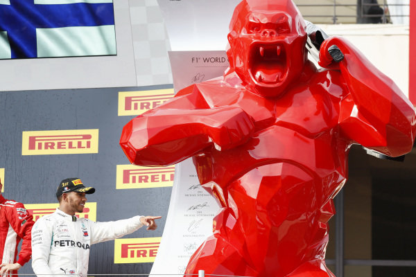 Lewis Hamilton, Mercedes AMG F1, 1st position, and a huge red gorilla on the podium.