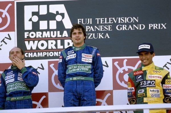 1990 Japanese Grand Prix.Suzuka, Japan.19-21 October 1990.Nelson Piquet (Benetton Ford) celebrates his 1st position with teammate Roberto Moreno, 2nd position and Aguri Suzuki (Lola Lamborghini) 3rd position on the podium.Ref-90 JAP 09.World Copyright - LAT Photographic