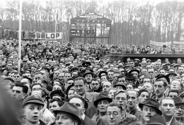 1938 Donington Grand Prix. Donington Park, Great Britain. 22 October 1938. Crowds watch the winners celebrations, atmosphere. World - LAT Photographic