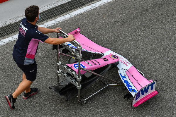 A Racing Point mechanic pushes a front wing along the pitlane