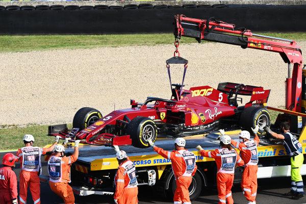 Marshals load the car of Sebastian Vettel, Ferrari SF1000, onto a truck